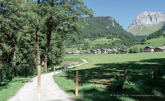 Wide view of cycle and footpath with mountains and village of La Chapelle d'Abondance in distance