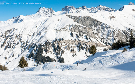 Skiers on piste above Areches Beaufort, French Alps