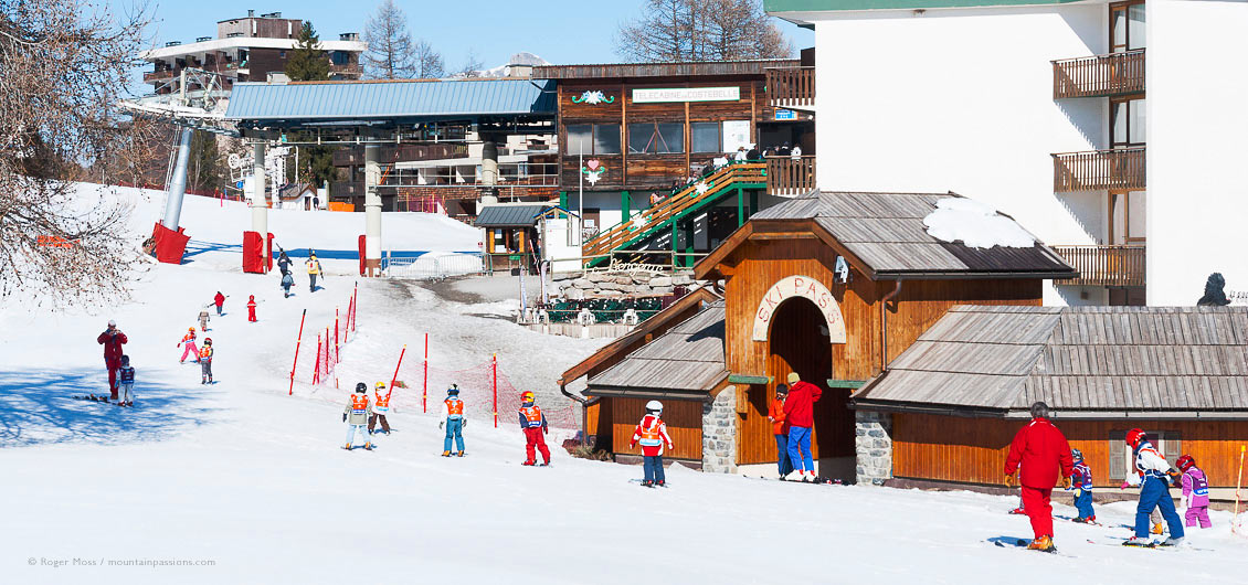 Children going to ski lesson, with chair lift and village in background