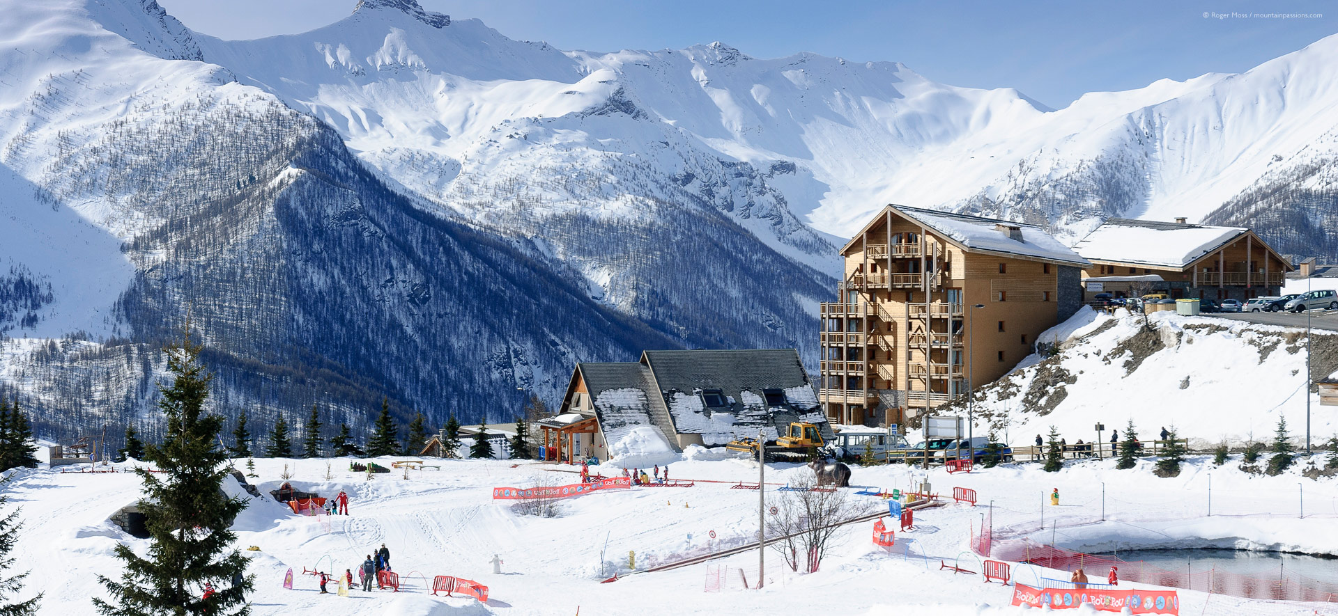 Wide view of children's ski school area, with apartments and mountains