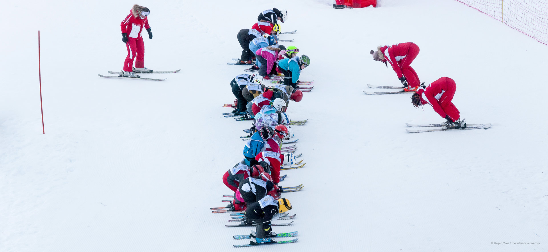 Bird's-eye view of ski instructors teaching children on the snow.