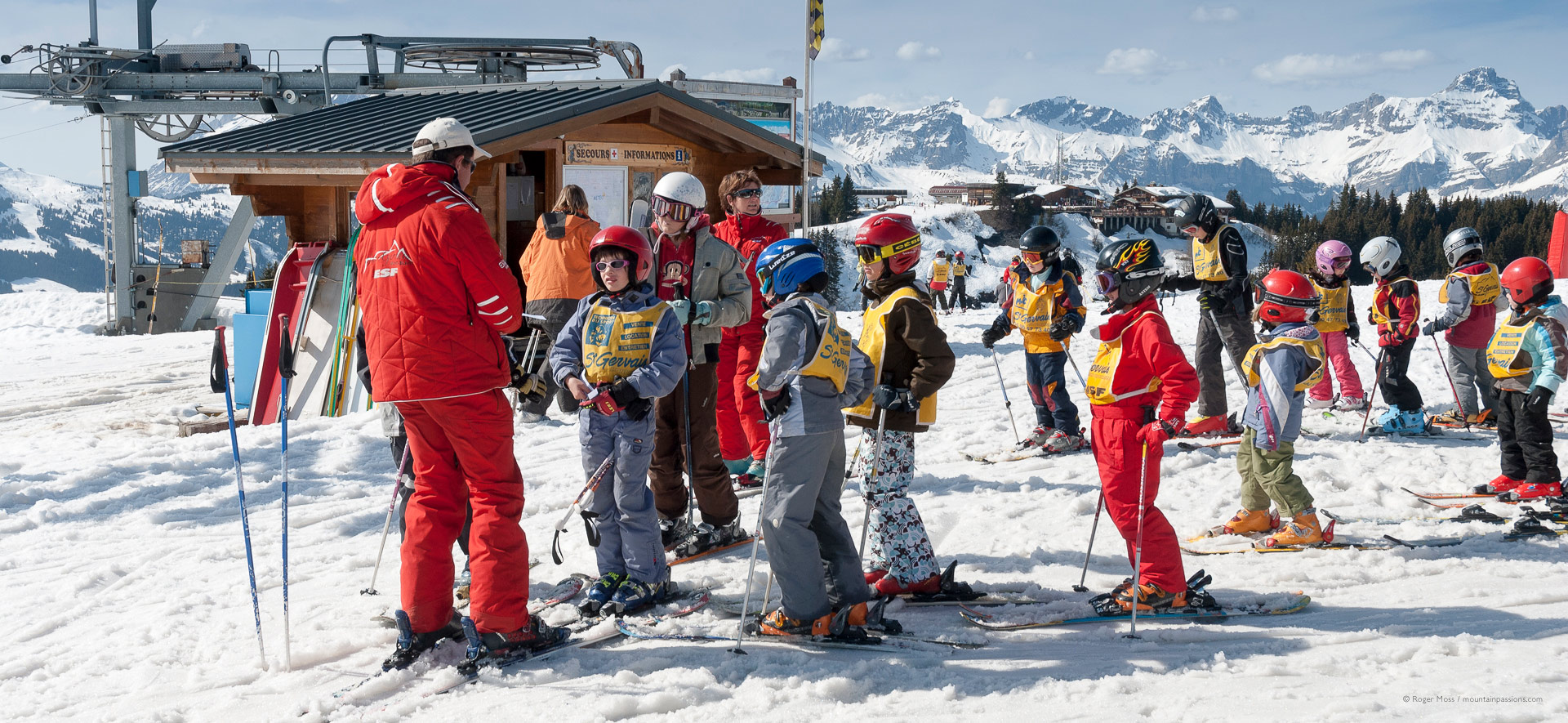 Young skiers gathering for ski lesson with ski instructor and mountains in background
