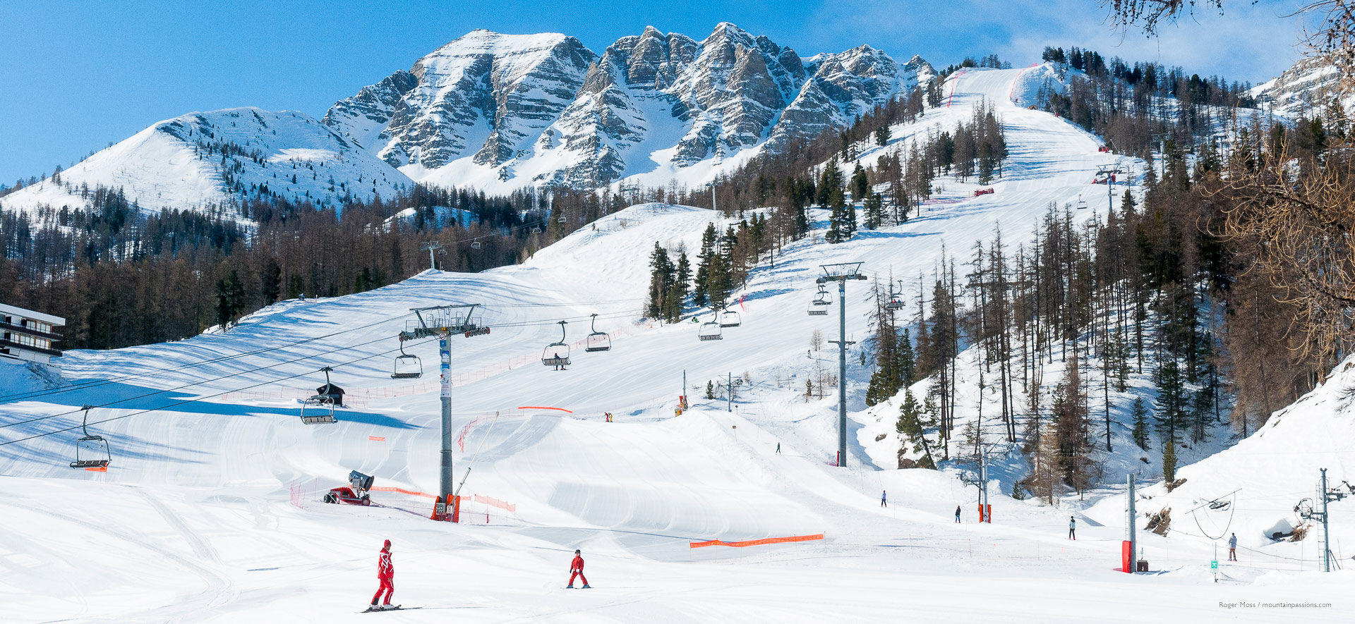 Early morning skiers on near-empty pistes, with trees and ski lifts