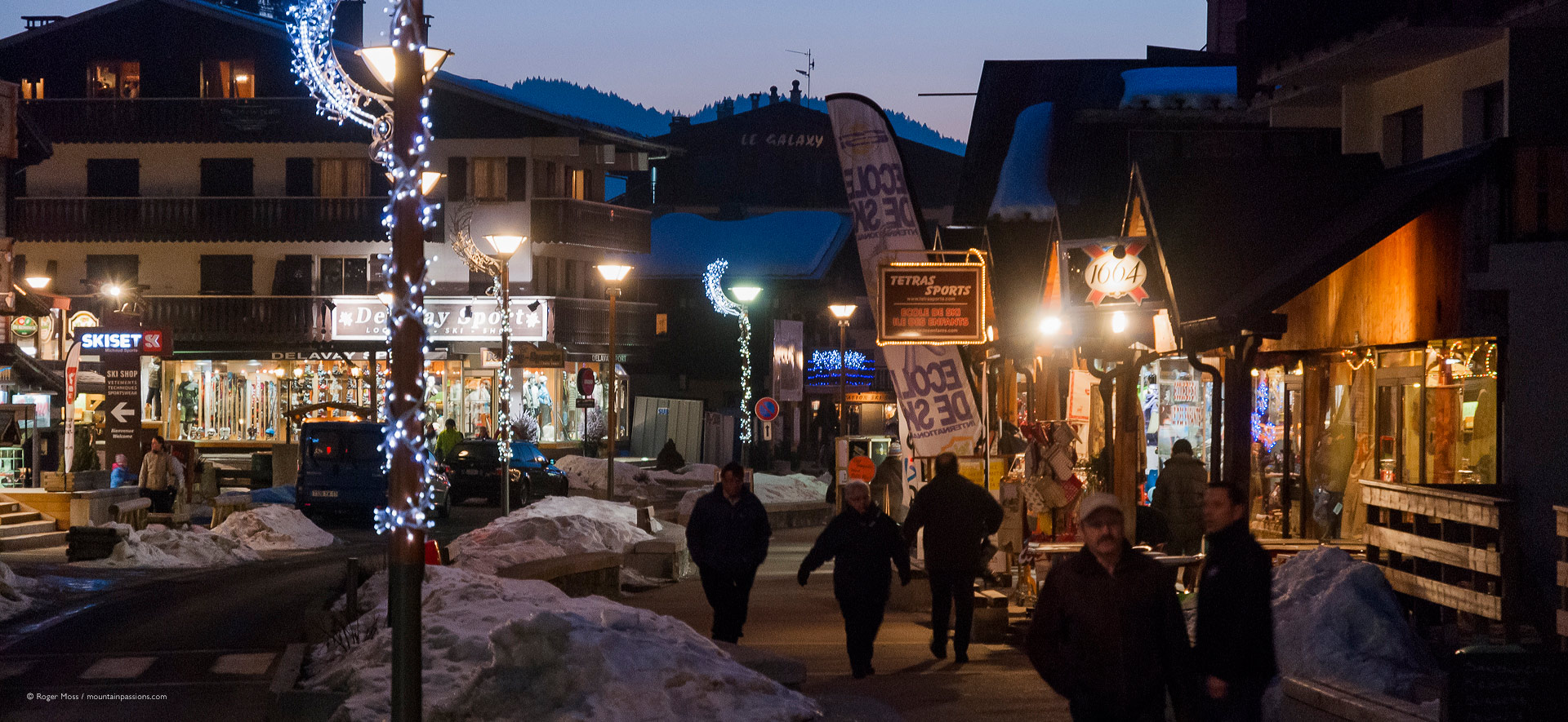Visitors in village centre at dusk, with boutiques and ski shops.