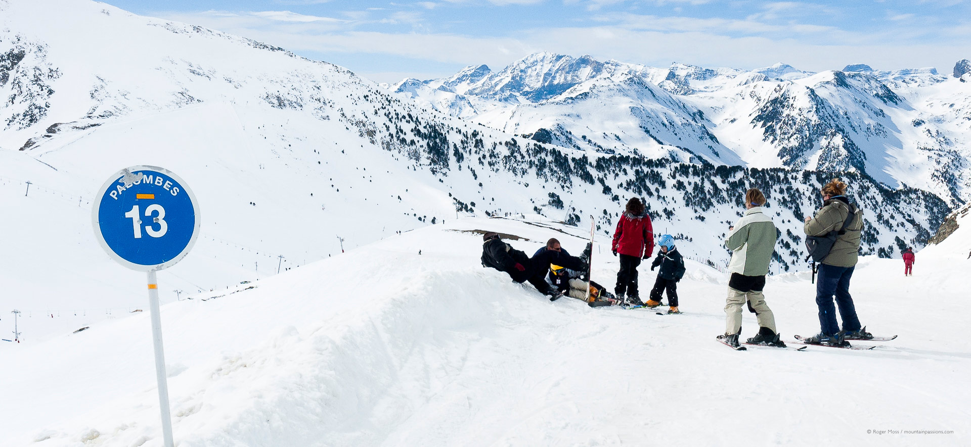 Family skiers adjusting snowboard bindings beside piste