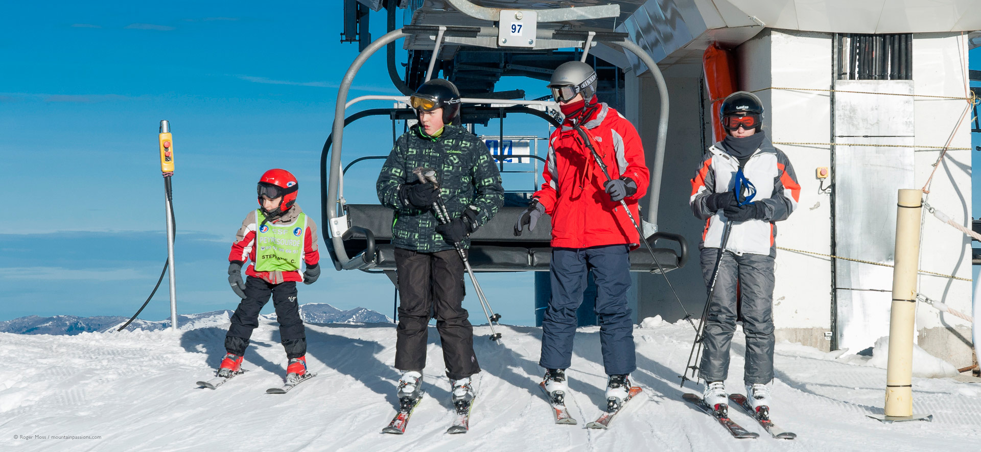 Skier family leaving top station of chair lift