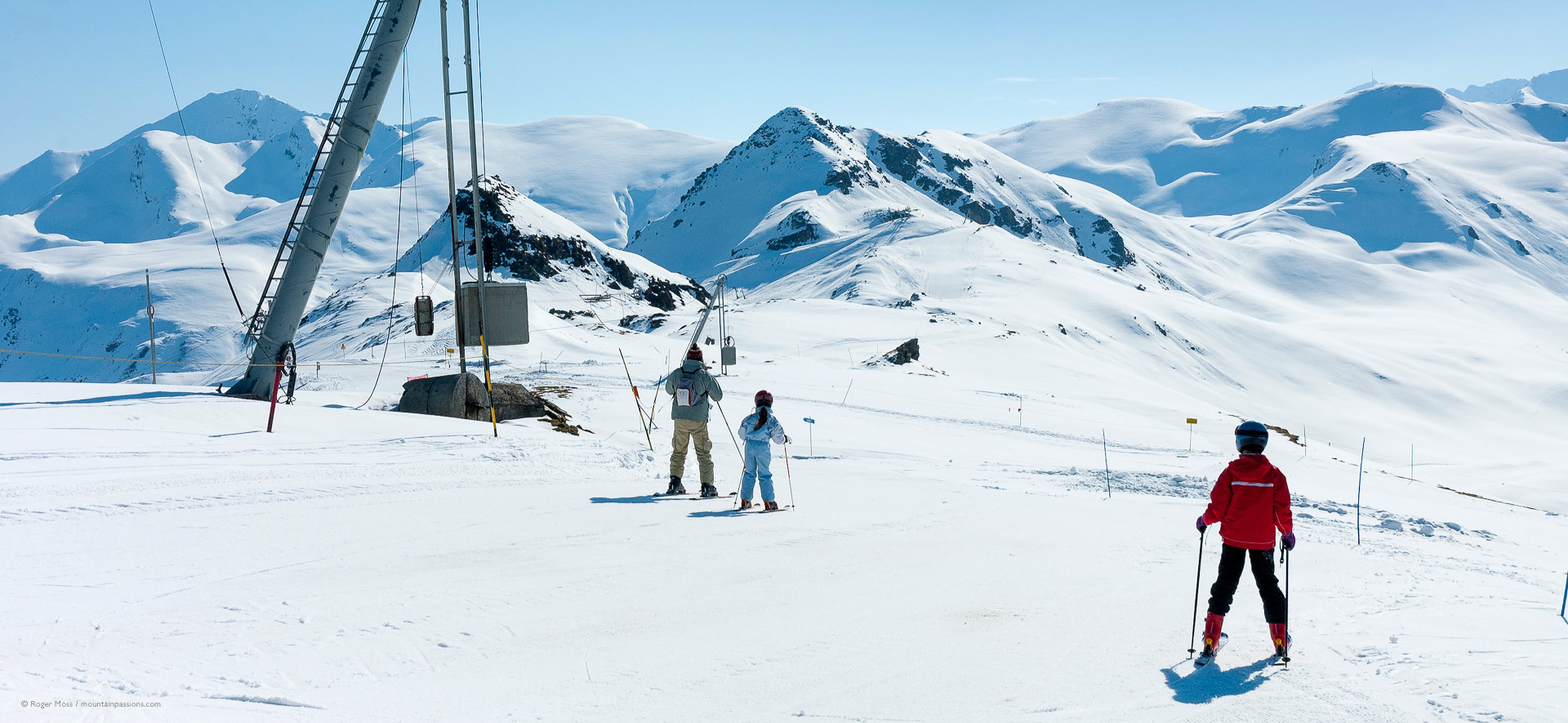 Family skiers beside drag-lift with wide mountain scenery