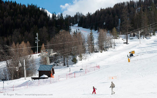 Family walking on ski piste with chairlift and forest
