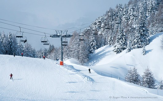 Forested pistes, chairlift and skiers, La Plagne