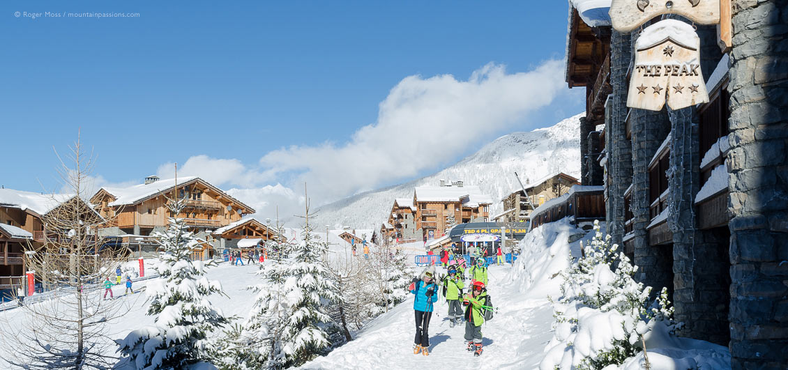 Skiers walking through Sainte Foy Tarentaise ski village, French Alps.
