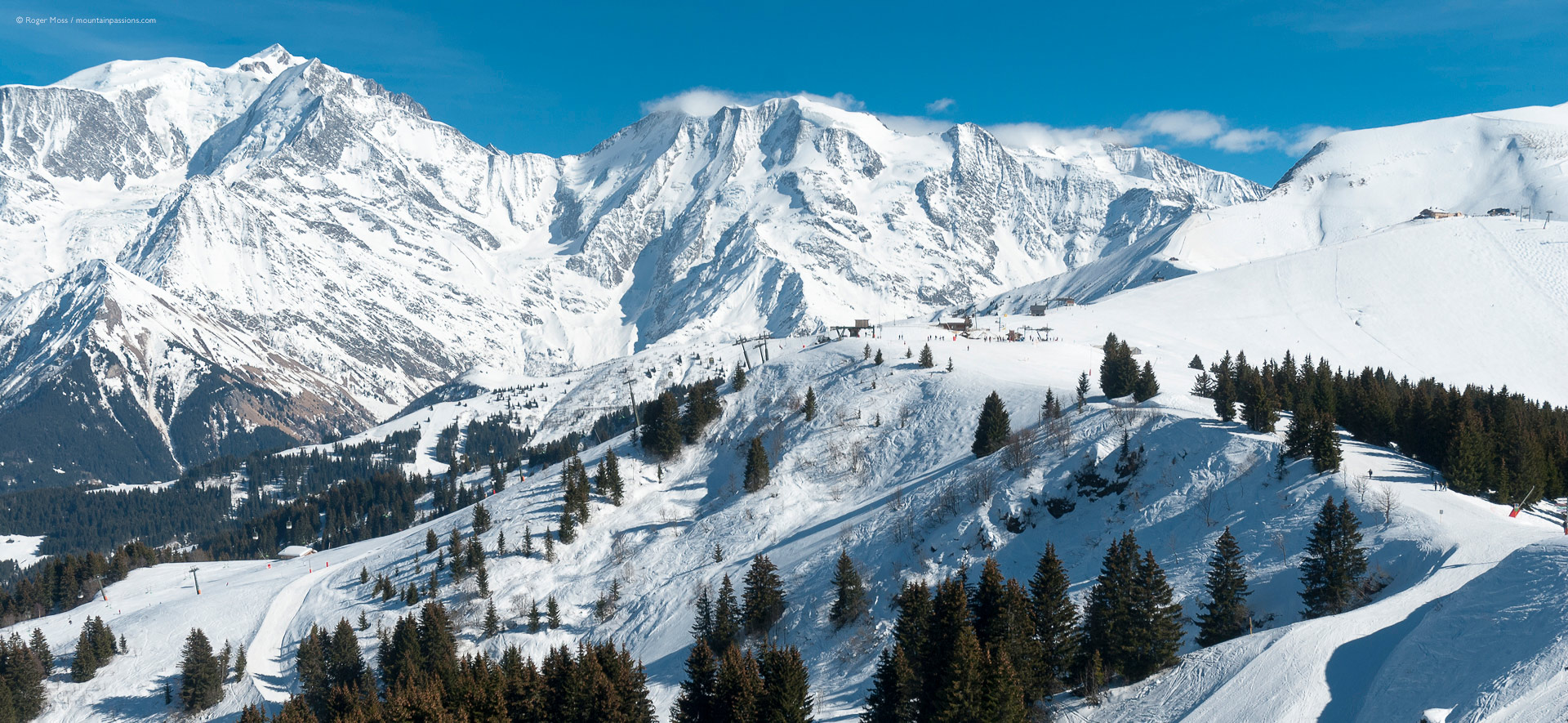Wide view of snow-covered mountains, with distant ski lift, pistes and Mont-Blanc in background.