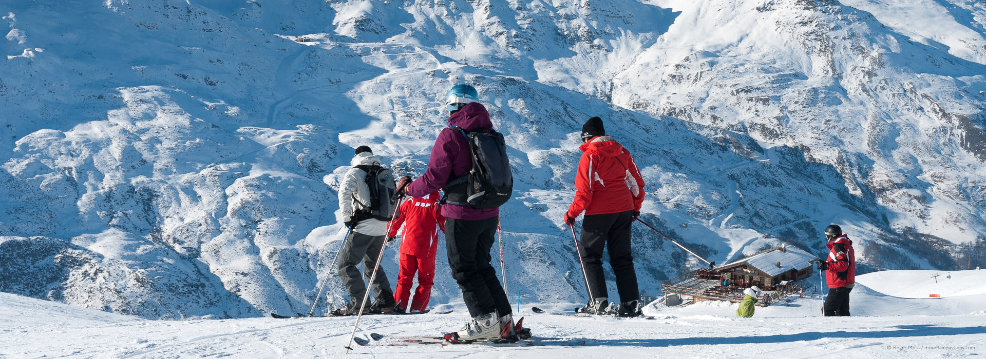 Group of skiers above mountain restaurant with snowy background.