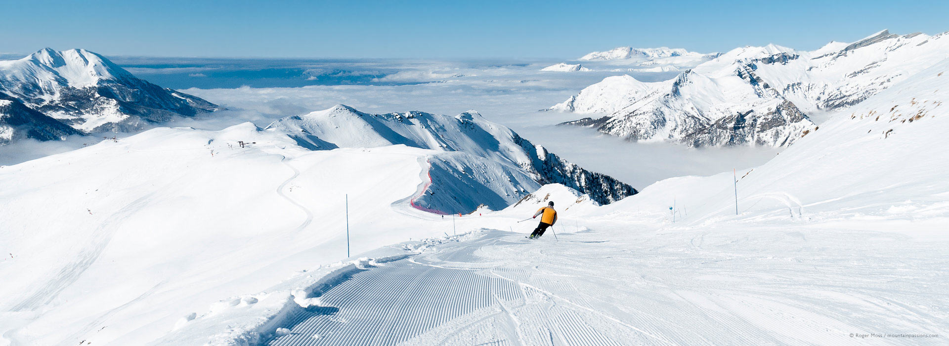 View of skier on wide piste above the clouds at Orcierès 1850.