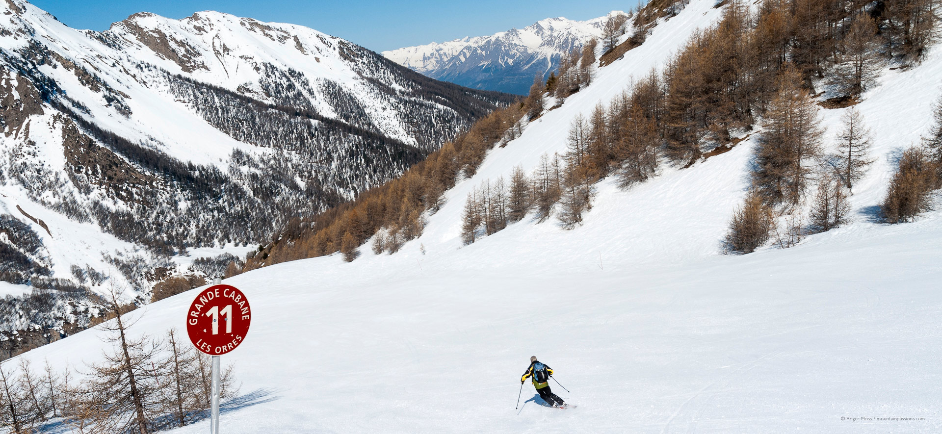 Lone skier descending red piste with beautiful mountain scenery.