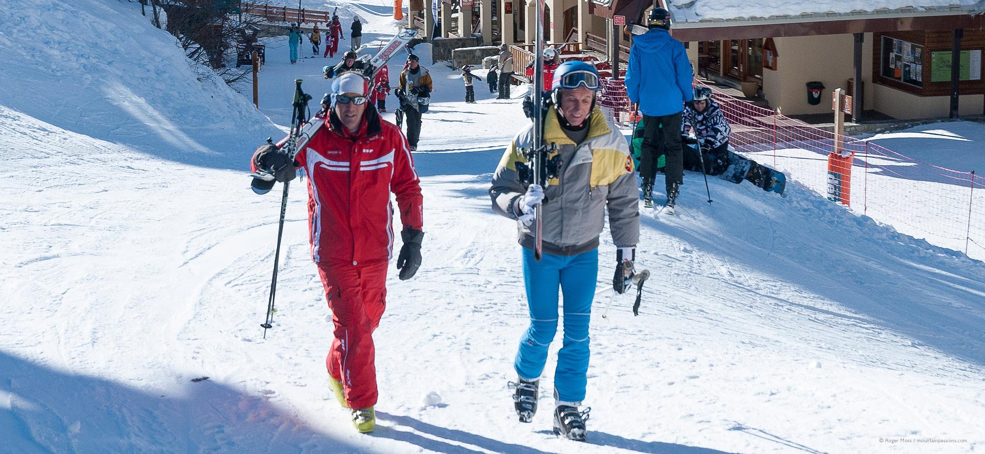 Skier with instructor walking through village