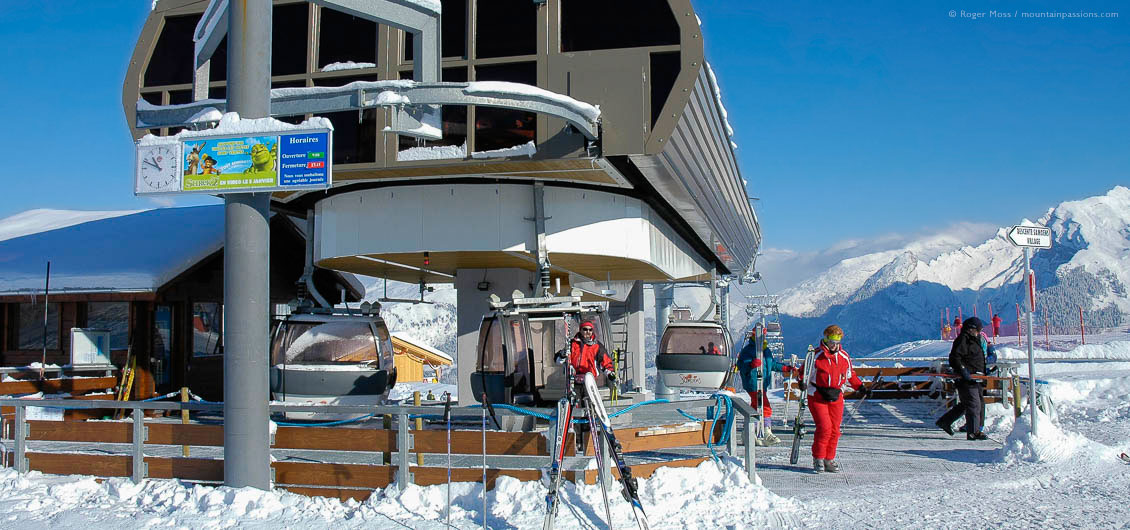 Skiers leaving high-speed gondola lift top station