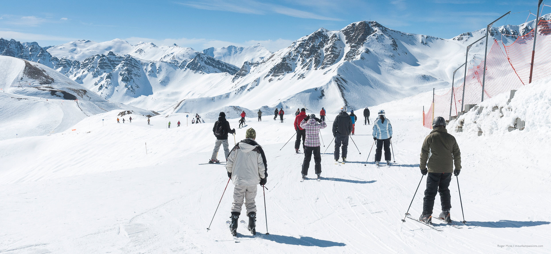Groups of skiers on wide piste between ski areas