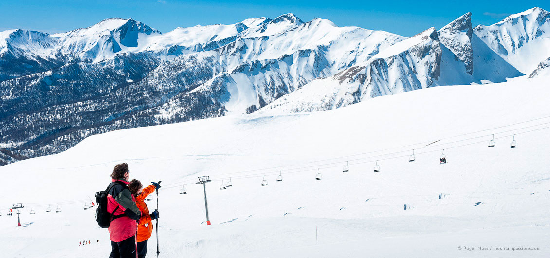 Wide view of two skiers admiring mountain scenery