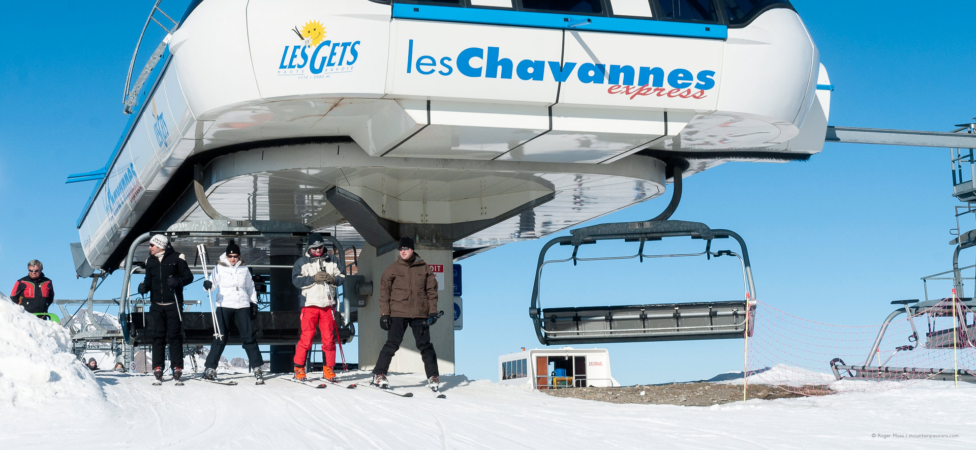 Skiers leaving high-speed chairlift above Les Gets.
