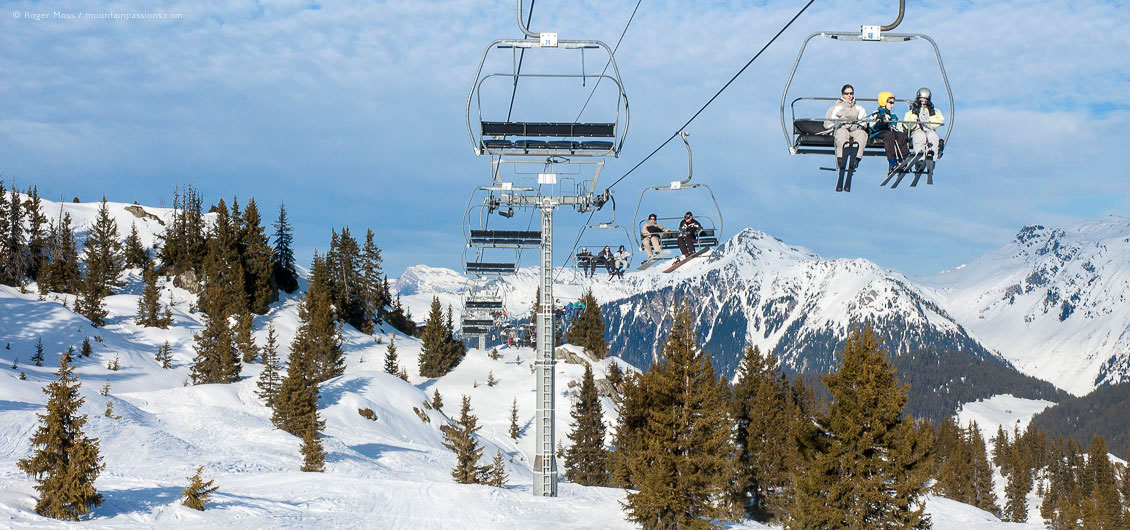 Wide view of skiers on chairlift above trees and ski terrain