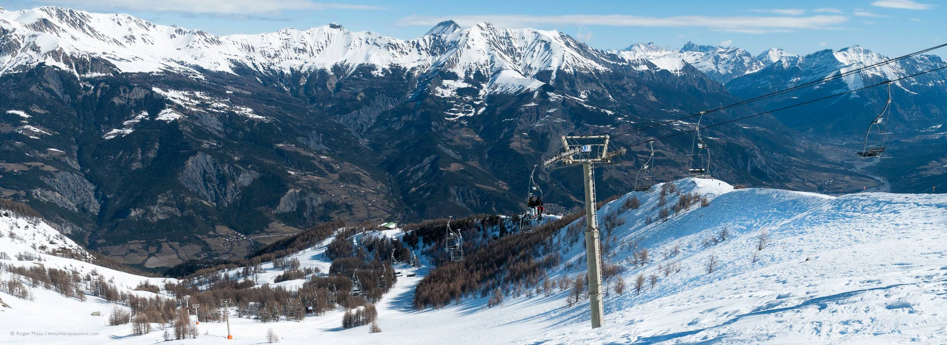 High, wide view of ski lift on mountainside with surrounding valleys at Pra Loup