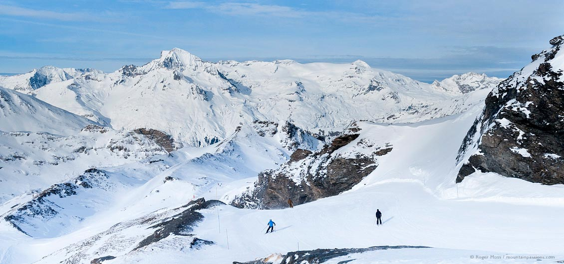 Wide view of two skiers descending high piste