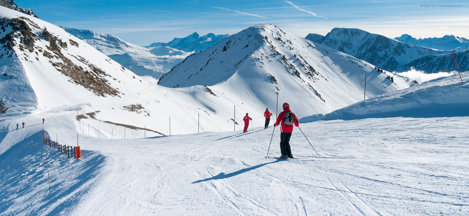 Skiers on upper piste, showing wide mountain views