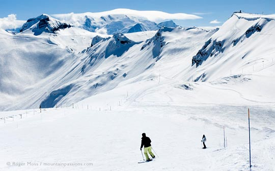Rear view of two skiers descending wide piste with big mountain view