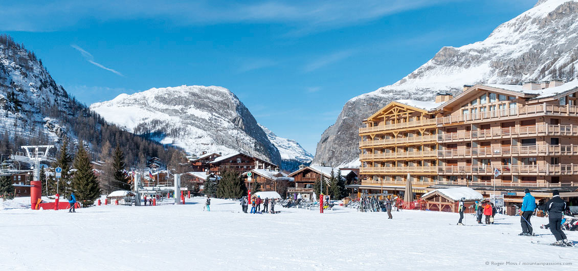 Wide view of skiers passing village apartment blocks, hotels and restaurants