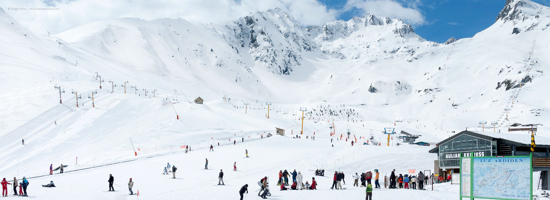 View of front-de-neige area, with skiers, chairlift and mountain background at Luz Ardiden