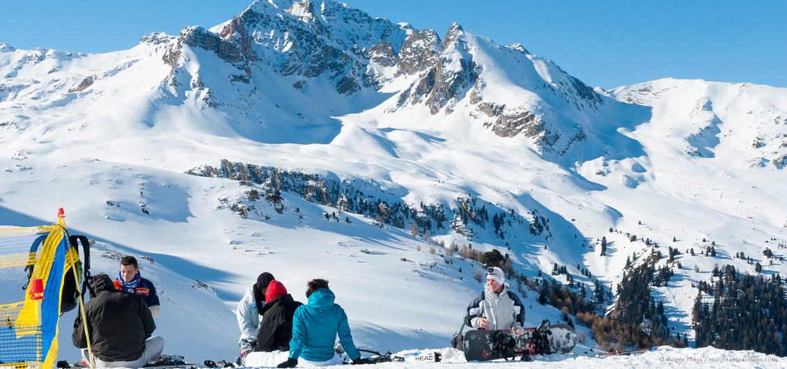 Young skiers and snowboarders picnic beside piste, with big mountain backdrop
