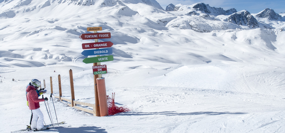 Skiers looking at piste map beside signage with big mountain view