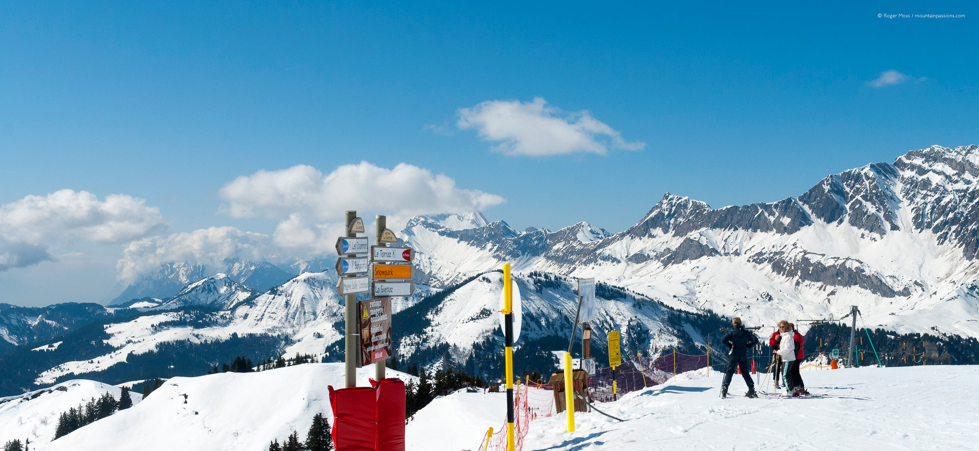 Wide view of skiers beside piste signage with mountains at Combloux.