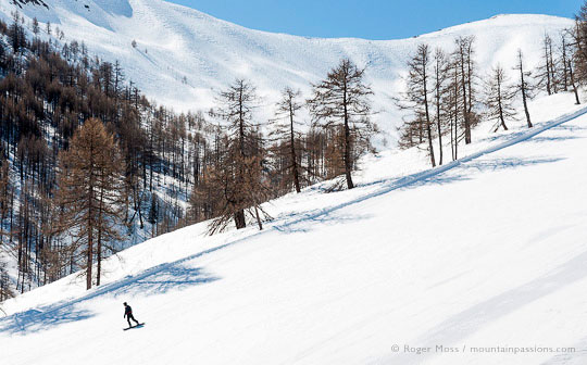 View from chairlift of snowboarder on piste with trees and mountains