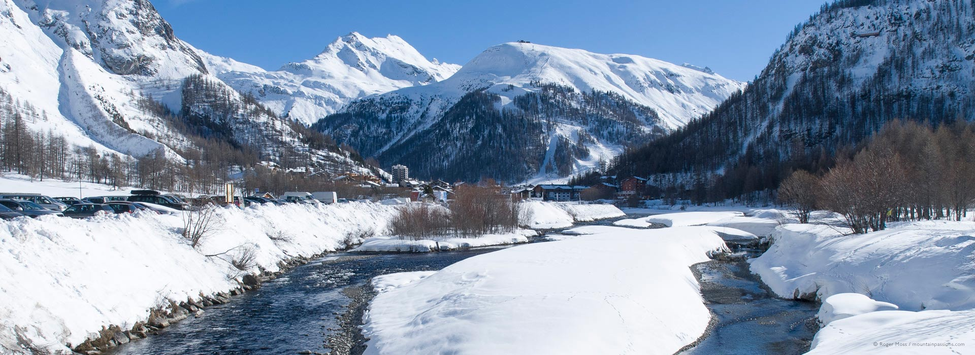 Wide view of river and snow-covered valley setting of Val d'Isere ski village.