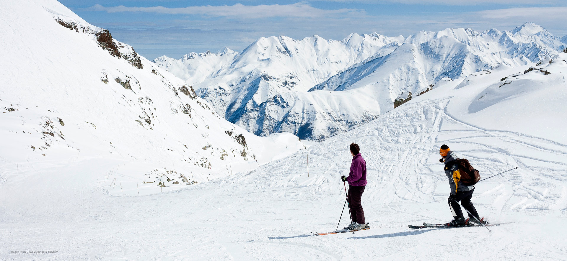 Two skiers on high altitude piste with big mountain views