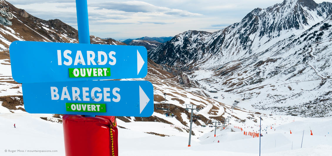 View from Col du Tourmalet with piste sign and La Mongie ski resort