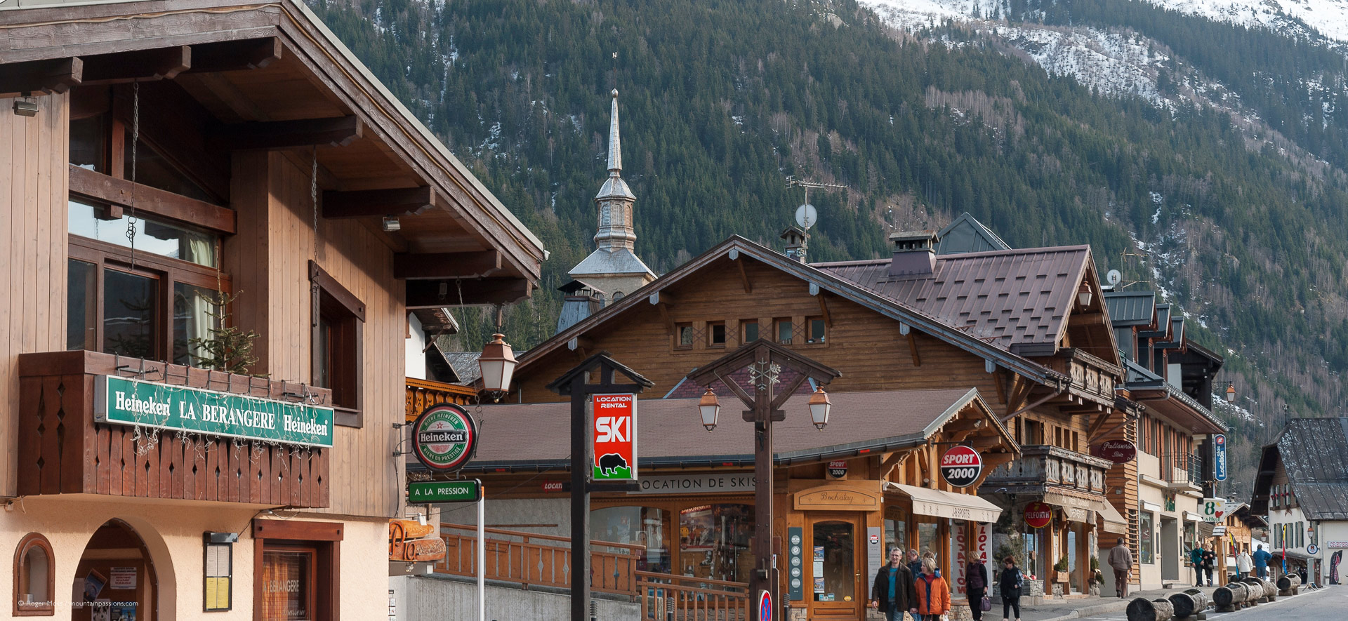 Chalet-style village centre with mountainside background.