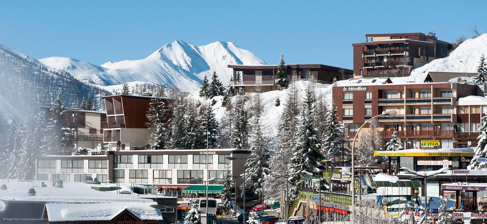 Side view of ski village with snow-covered trees and mountains