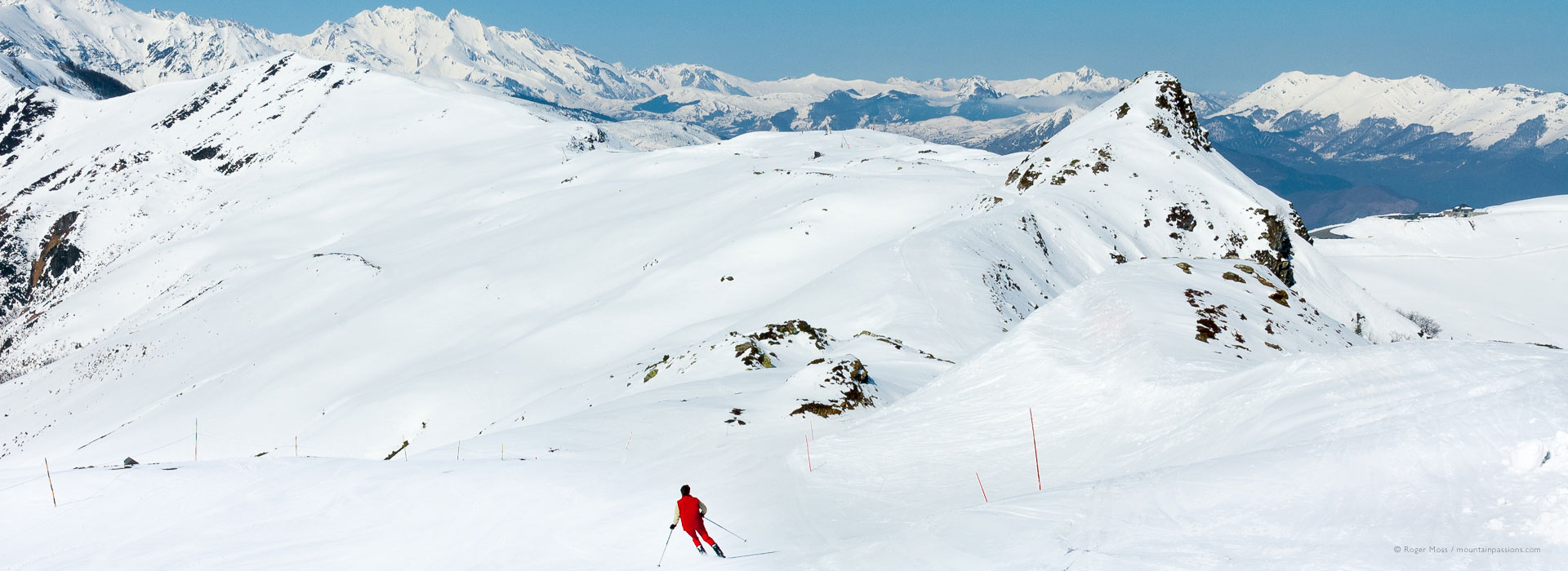 Wide view of mountain scenery with skier on piste at Hautacam.