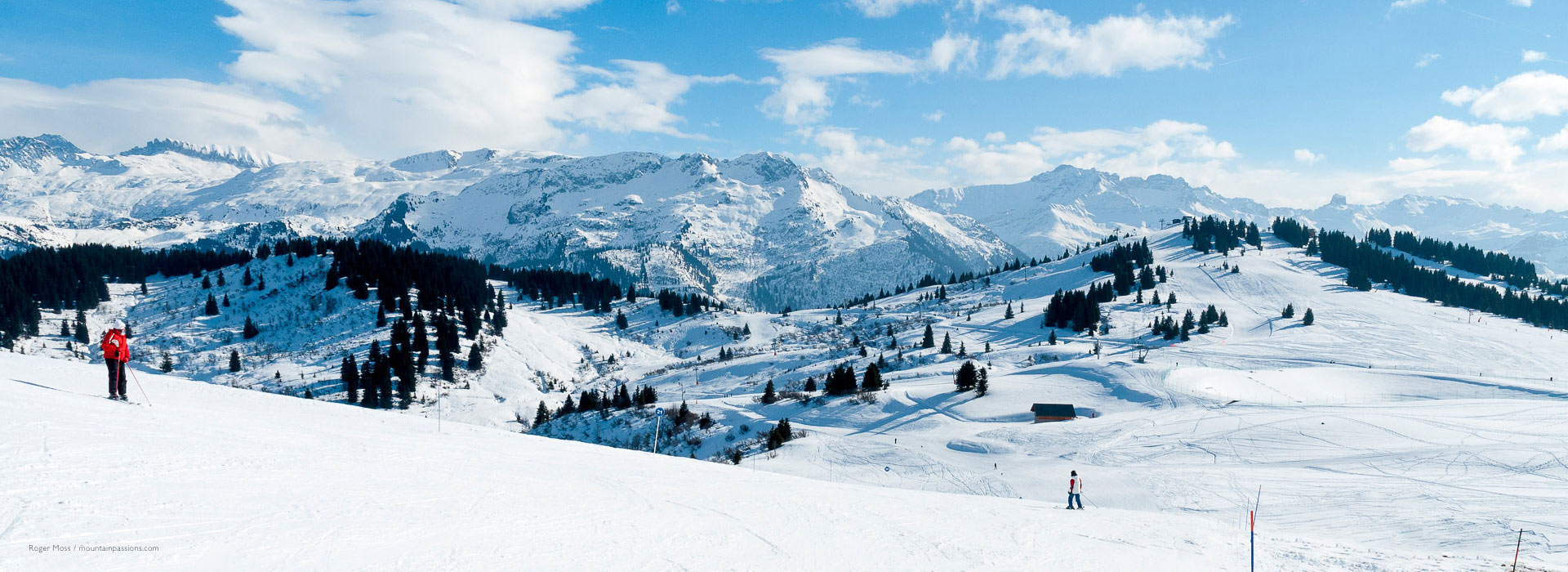 Skiers on wide piste with panoramic view of mountain landscapes at Les Saisies