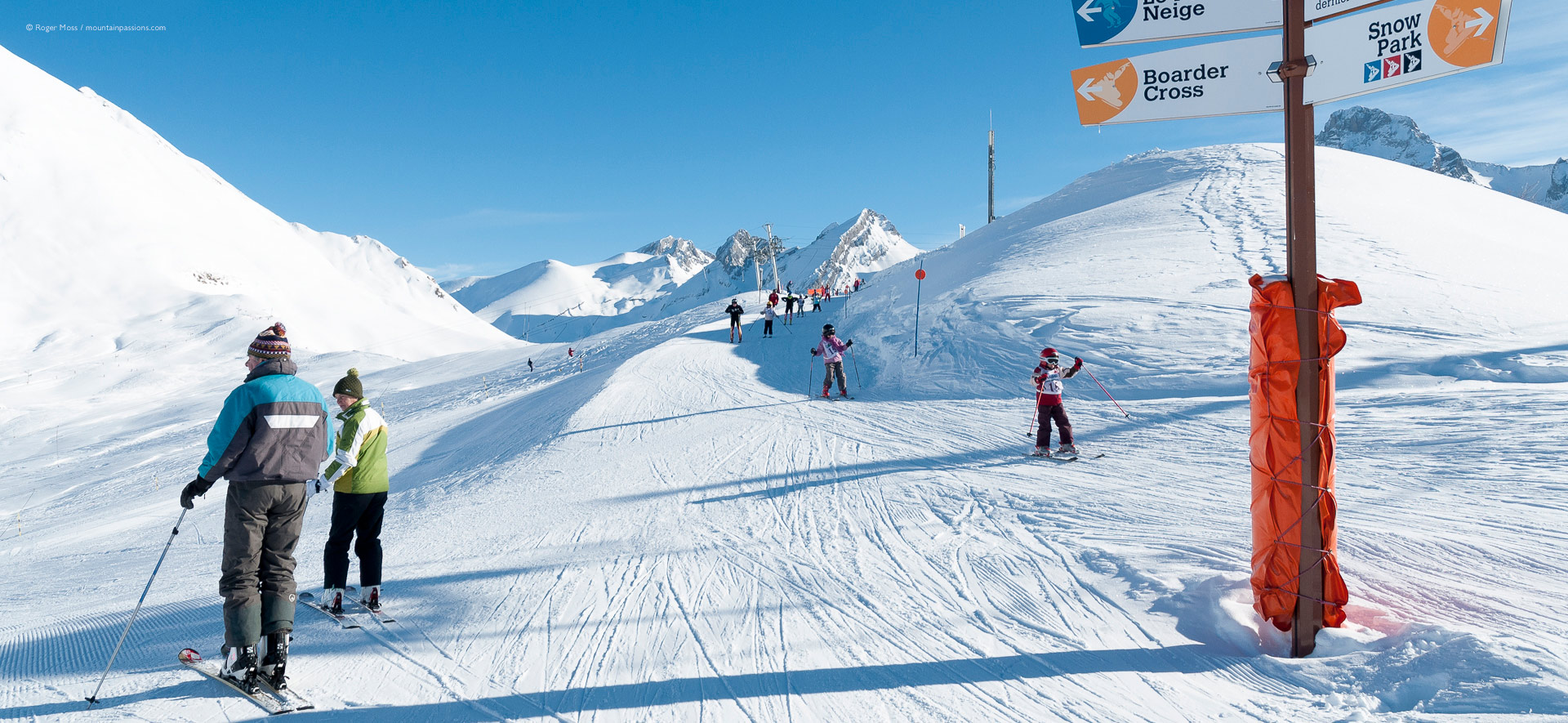 Older skiers being passed by ski school children's group