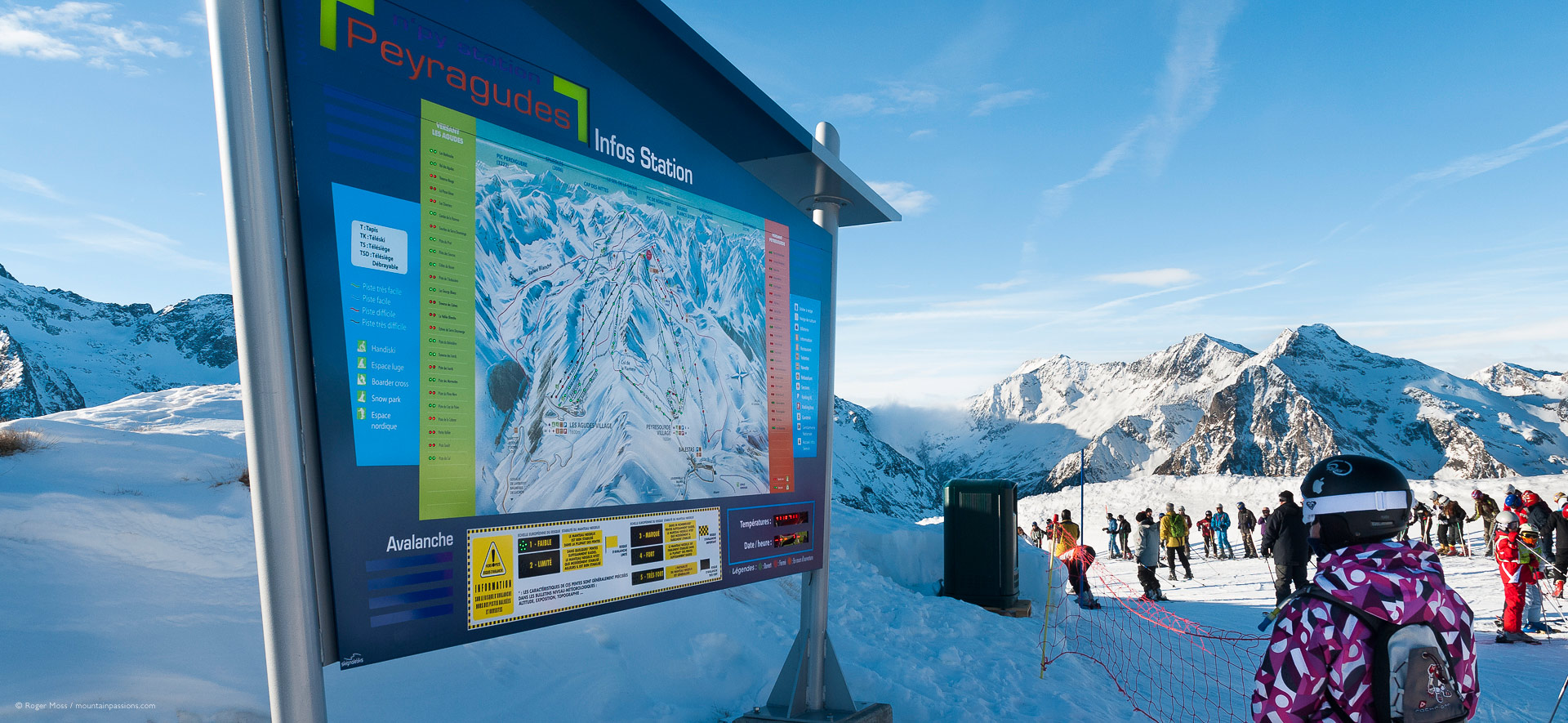 Young skier beside piste map sign.