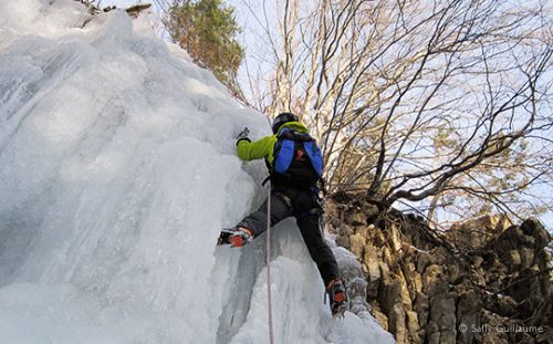 Close-up of climber nearing top of frozen waterfall