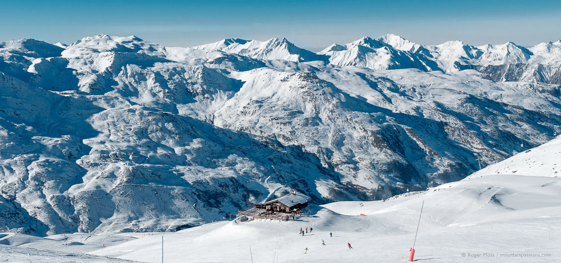 High, wide view of skiers heading for mountain restaurant in Les menuires ski resort with mountains in background