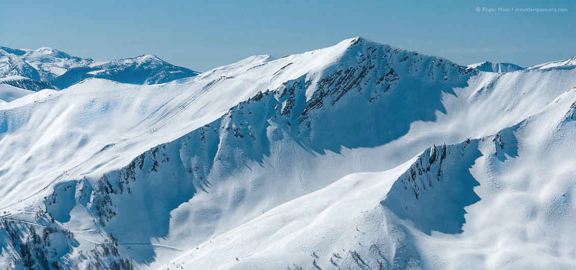 Wide view towards snow-covered mountains, showing ski-pistes between Pra Loup and Val d'Allos