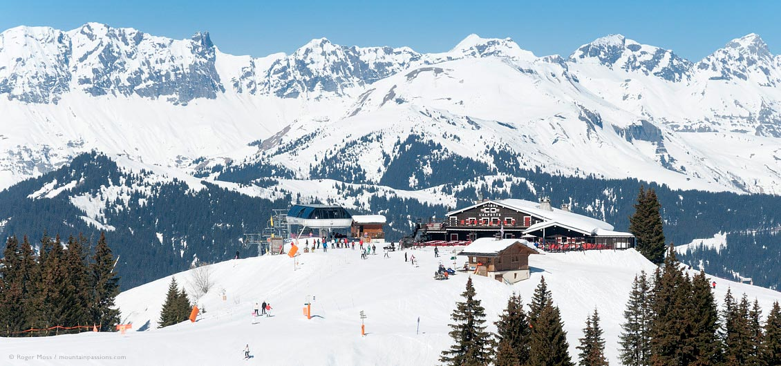 High view of l'Alpette mountain restaurant with skiers and chair-lift