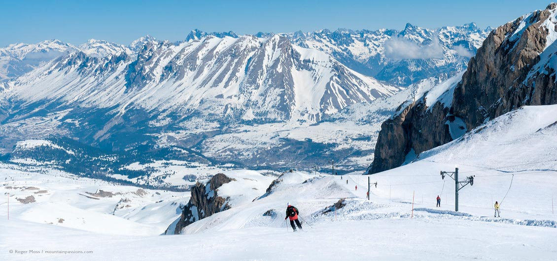 Wide view of skier on piste beside drag-lift with snow-covered valley and mountains in background