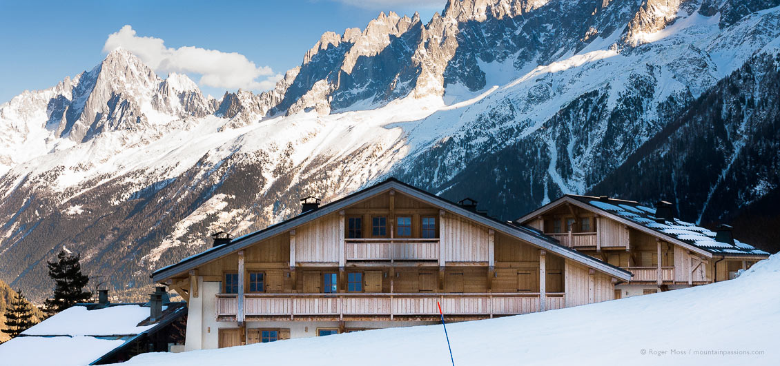 Piste-side, chalet-style apartments with mountains in late afternoon light above Les Houches