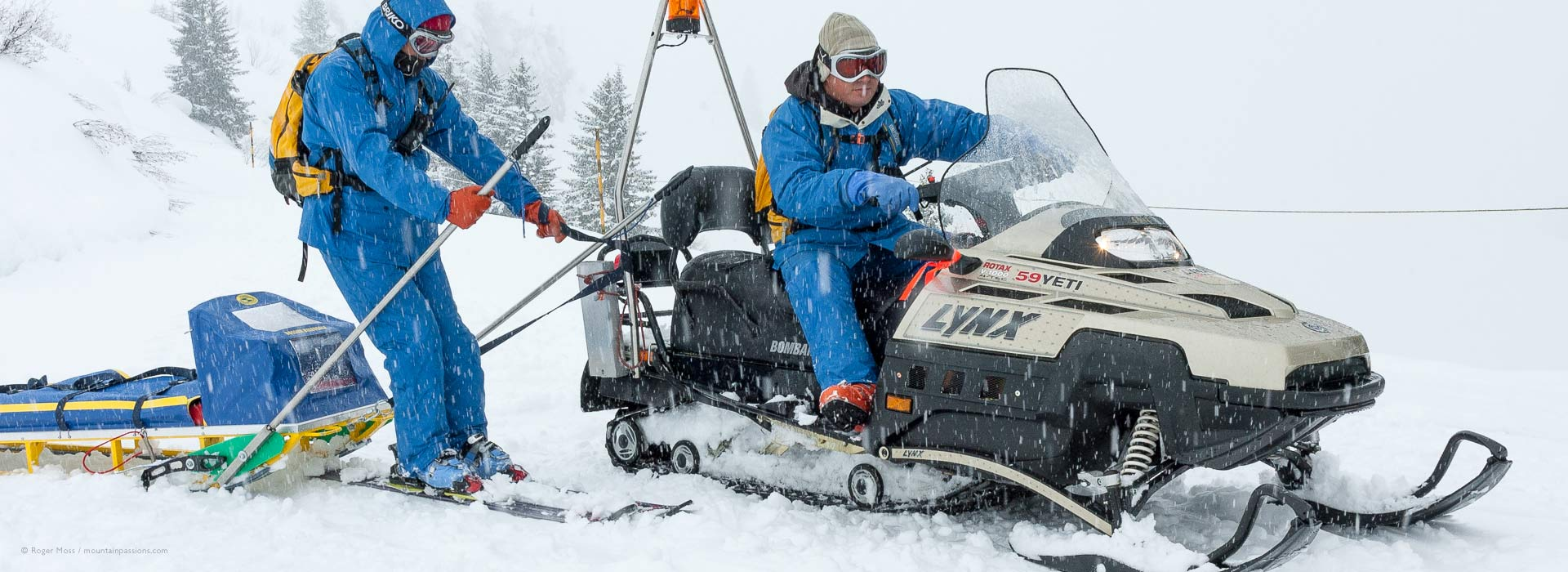 Behind the scenes ski patrol team with snowmobile practice with an accident recovery sled